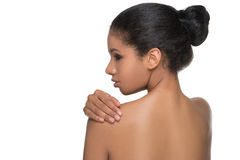 Body care. Rear view of beautiful naked woman standing back to camera and holding her hand on shoulder while isolated on white Stock Photo