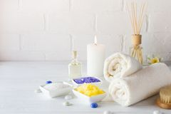 Body care set for peeling. With towel,white lily, sea salt, bath oil, sugar body scrub, massage brush. And candle stock images