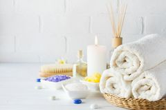 Body care set for peeling. With towel,white lily, sea salt, bath oil, sugar body scrub, massage brush. And candle stock photos
