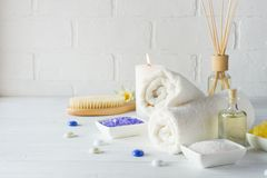 Body care set for peeling. With towel,white lily, sea salt, bath oil, sugar body scrub, massage brush. And candle stock photo
