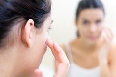 Body care. Woman applying cream on face. Body care. Close up portrait of Woman applying cream on face Stock Photos
