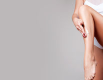 Body care. Woman applying moisturizer cream on legs. Closeup of woman`s legs with perfect skin Royalty Free Stock Photo