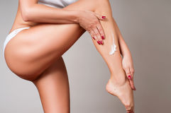 Body care. Woman applying moisturizer cream on legs. Closeup of woman`s legs with perfect skin Stock Photos