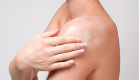 Body care. Woman cares about her shoulder applying cosmetic cream Royalty Free Stock Photos