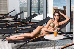 Body care. Woman with perfect body in bikini lying on the deckchair by swimming pool Royalty Free Stock Photos