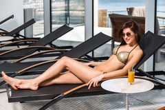 Body care. Woman with perfect body in bikini lying on the deckchair by swimming pool Royalty Free Stock Image