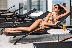 Body care. Woman with perfect body in bikini lying on the deckchair by swimming pool Royalty Free Stock Images