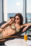 Body care. Woman with perfect body in bikini lying on the deckchair by swimming pool Stock Photo