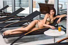 Body care. Woman with perfect body in bikini lying on the deckchair by swimming pool. At resort spa hotel Royalty Free Stock Photography
