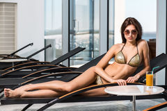 Body care. Woman with perfect body in bikini lying on the deckchair by swimming pool. At resort spa hotel Stock Photo