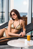 Body care. Woman with perfect body in bikini lying on the deckchair by swimming pool Stock Image