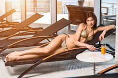 Body care. Woman with perfect body in bikini lying on the deckchair by swimming pool Stock Photos