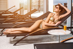 Body care. Woman with perfect body in bikini lying on the deckchair by swimming pool. At resort spa hotel Stock Photos