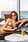 Body care. Woman with perfect body in bikini lying on the deckchair by swimming pool. At resort spa hotel Stock Images