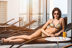 Body care. Woman with perfect body in bikini lying on the deckchair by swimming pool. At resort spa hotel Royalty Free Stock Photos