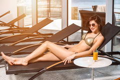 Body care. Woman with perfect body in bikini lying on the deckchair by swimming pool Royalty Free Stock Photo