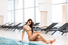 Body care. Woman with perfect body in bikini lying near the deckchair by swimming pool Stock Photos