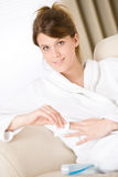 Body care - woman remove nail polish in bathrobe Royalty Free Stock Photography