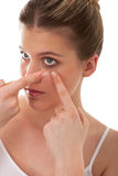 Body care - Young woman apply contact lens. On white background Royalty Free Stock Photos