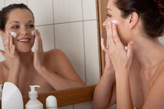 Body care - Young woman apply cream Royalty Free Stock Photography