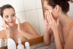 Body care - Young woman apply cream. In the bathroom Stock Photos