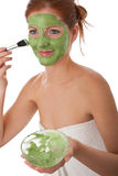 Body care - Young woman apply facial mask. Body care - Young woman apply green facial mask on white background Stock Images