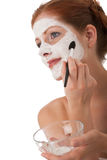 Body care - Young woman apply facial mask. Body care - Young woman apply white facial mask on white background Royalty Free Stock Image