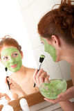 Body care - Young woman apply facial mask. Body care - Young woman apply green facial mask in the bathroom Stock Image