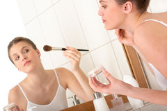 Body care - Young woman apply powder. Body care - Young woman applying powder in front of the mirror in the bathroom stock photos