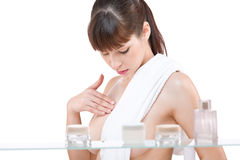 Body care: Young woman applying lotion Stock Photography