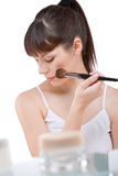 Body care: Young woman applying powder with brush Stock Images
