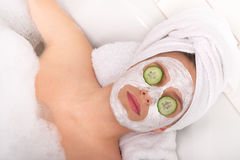 Body care - Young woman with facial mask. And cucumber on eyes Royalty Free Stock Photos