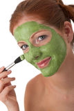 Body care - Young woman with facial mask. Body care - Young woman with green facial mask on white background Royalty Free Stock Photos