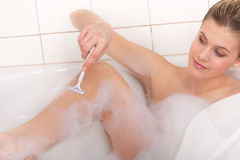 Body care - Young woman shave legs Royalty Free Stock Image