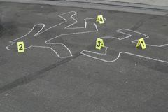 Body Chalk Outline w Number Markers. Chalk outlines of bodies  on a street with number markers Royalty Free Stock Photography