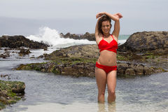 Body Confidence. Pretty girl in a red bikini posing and smiling for the camera at the Seaside Royalty Free Stock Photo
