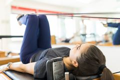 Body Conscious Woman Exercising On Pilates Reformer Machine. Full length of body conscious woman exercising on pilates reformer machine in gym royalty free stock photos