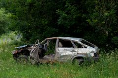 The body of a crashed car drowned in mud. Stands on the grass stock images