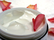 Body cream with rose petals 4. Body cream with rose petals on white towel, closeup Stock Photography