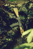 Body of dead soldier. Dead body of killed soldier in war dressed in military ammunition laying on ground with rifle outdoor royalty free stock images
