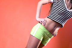 Body Detail Young Woman. Body detail of a young woman wearing green shorts and a black and white horizontal stripe cropped top.  Shown from the knees to the neck Stock Image