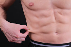 Body fat percentage. Muscular man measures level of fat on his body close up. Stock Photography
