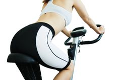 Body of fitness woman. Isolated young beautiful woman siting and riding on a spinning bicycle from back view (only body Royalty Free Stock Image