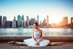 Body flexibility of classical ballet dancer. Ballerina in white dress sits on a twine, front view, cityscape with skyscrapers on background Stock Photography