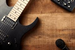 Body and fretboard of modern electric guitar and a microphone on rustic wooden background. stock photography