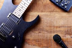 Body and fretboard of modern electric guitar, Multi effects Processor and microphone on rustic wooden background. Top view. Copy space royalty free stock photos