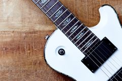 Body and fretboard of modern electric guitar on rustic wooden background. Top view. Copy space stock image