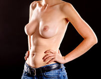 Body of a girl with naked breasts in jeans. Royalty Free Stock Photos