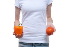 Body of girl with pepper and tomato in the hands Stock Photography