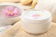 Body, Hand and Face Cream. Soft body, hand and face cream with pink petals on top in a bathroom/spa setting (Selective Focus, Focus on the horizontal/back petal Royalty Free Stock Photography